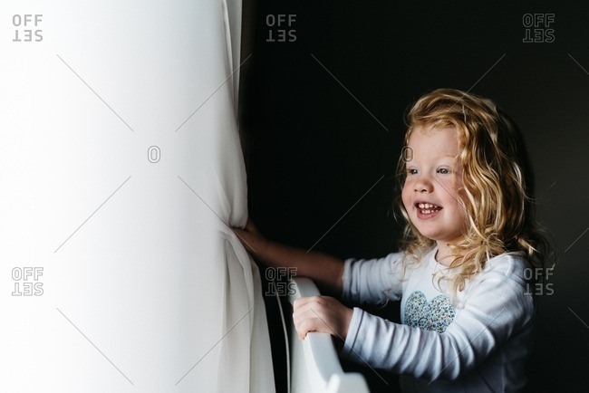 Girl smiling while looking out window