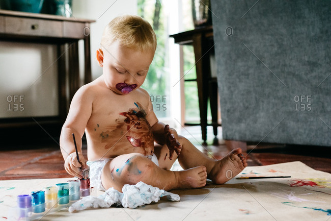 Toddler girl making mess with paints