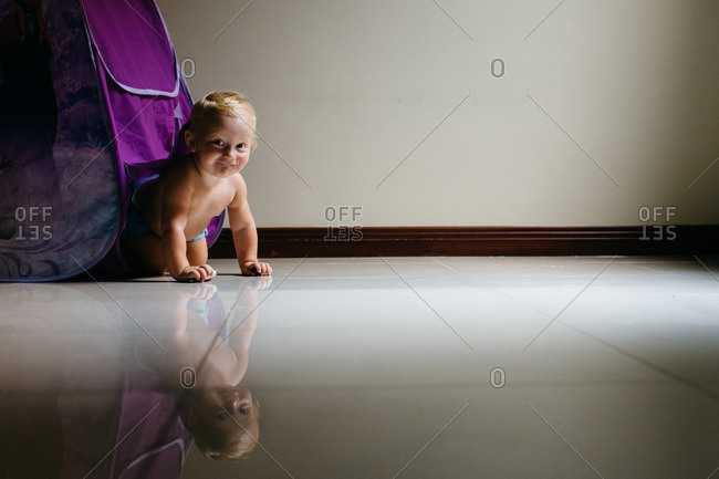 Toddler crawling on reflective floor