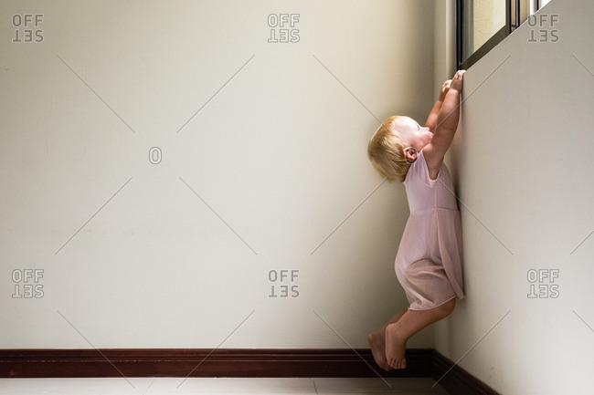 Toddler girl hanging from windowsill