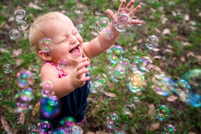 Toddler girl laughing with bubbles