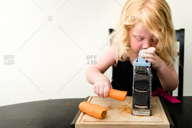 Girl grating a raw carrot