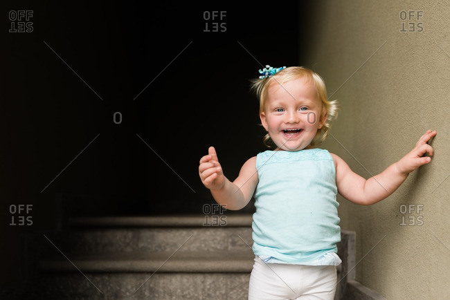 Toddler girl laughing in stairway