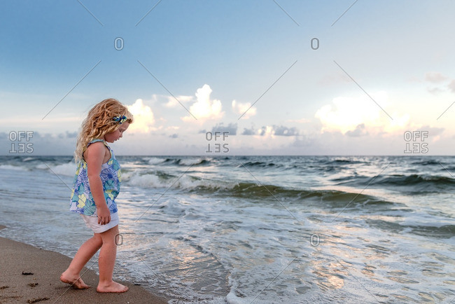 Girl on beach looking at waves