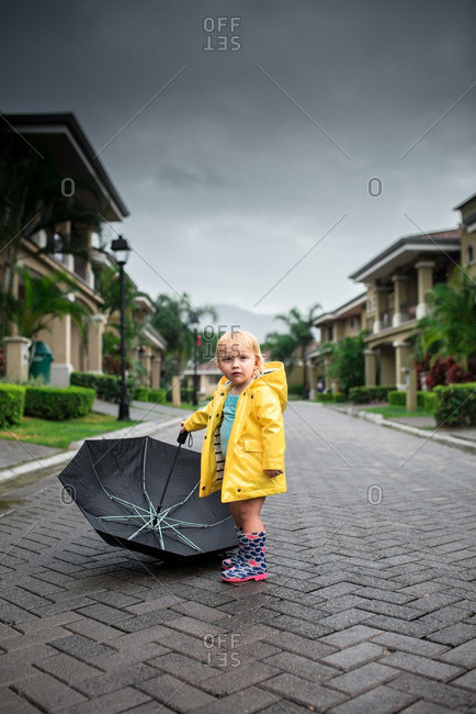 Girl in street with umbrella in stormy setting