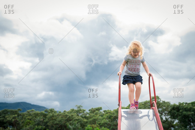 Girl standing at top of slide