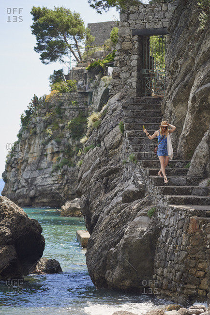 Woman going down coastal steps in Italy