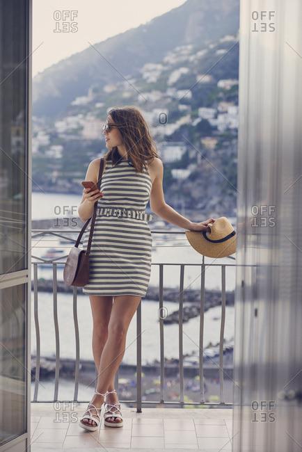 Woman on balcony in scenic coastal Italy