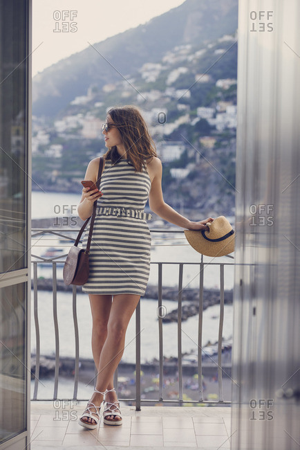 Woman on balcony in scenic coastal Italy