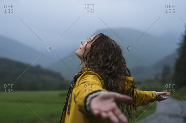 Woman in rain with open arms