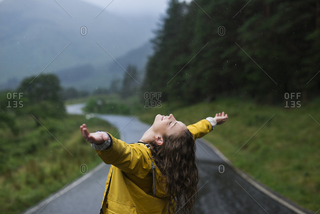 Woman in rural rain with open arms