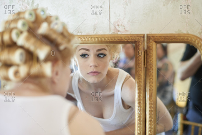 Bride looking in the mirror while getting ready