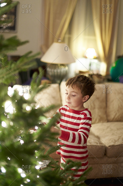 Young child trimming a Christmas tree