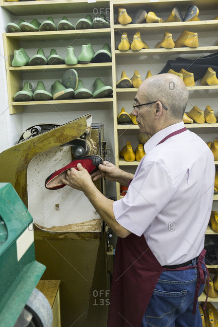 Shoemaker using a machine in his workshop