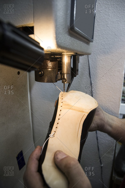 Shoemaker sewing the sole of a shoe using a machine in his workshop