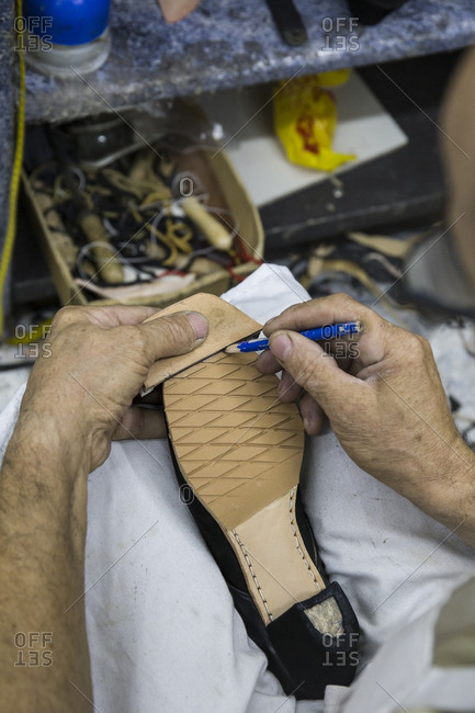 Shoemaker marking the sole of a shoe with a pencil