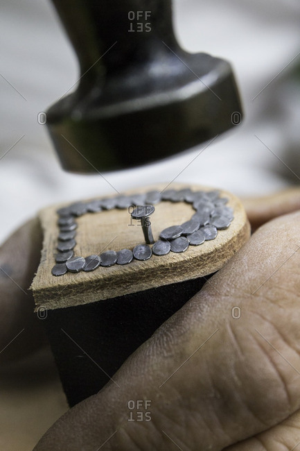 Shoemaker nailing nails in the heel of a shoe