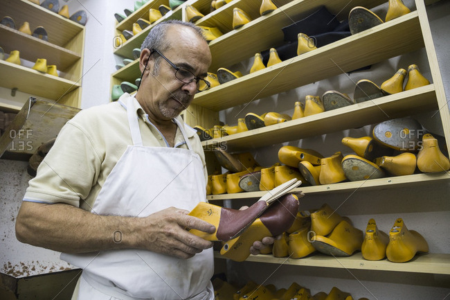 Shoemaker selecting shoe lasts from a shelf in his workshop