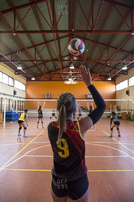 Volleyball player serving the ball during a volleyball match