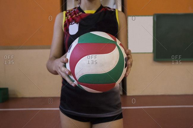 Volleyball player prepared to serve holding the ball during a volleyball match