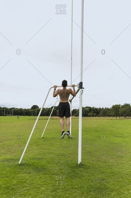 Athlete doing chin-ups on sports field