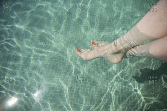 Female feet in swimming pool