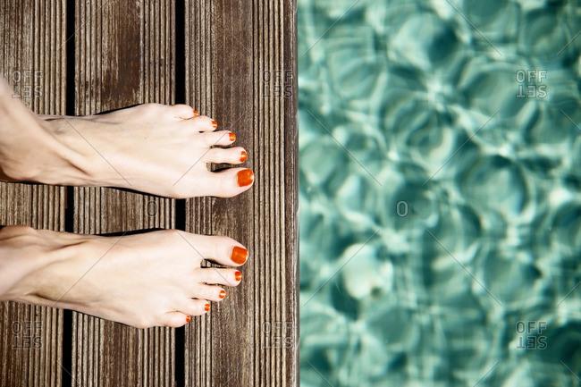 Female feet standing at pool's edge