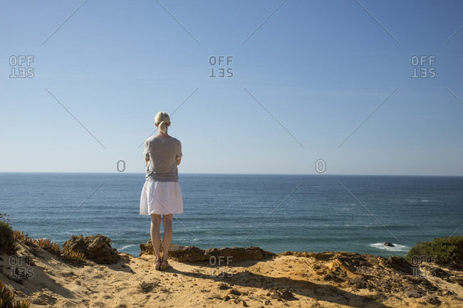 Woman standing at coast- looking at distance