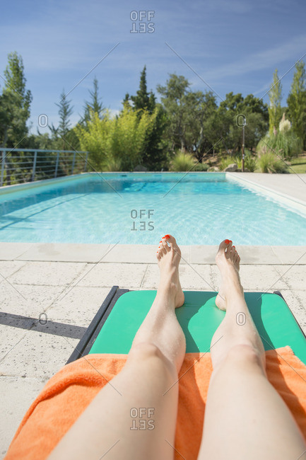 Woman tanning at swimming pool