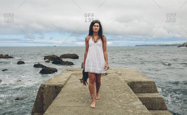 Barefoot woman walking on pier