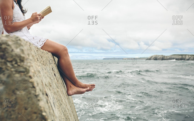 Barefoot woman sitting on pier reading a book- partial view