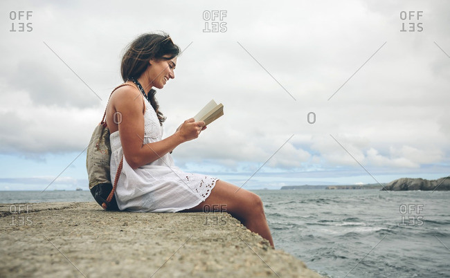 Smiling woman with backpack sitting on pier reading a book