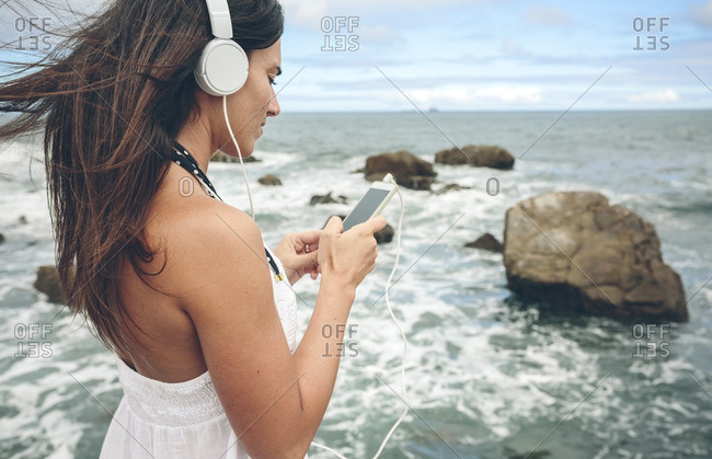 Woman listening music with headphones and smartphone in front of the sea