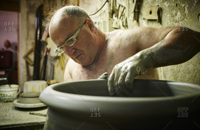 Potter in workshop working on large terracotta vase