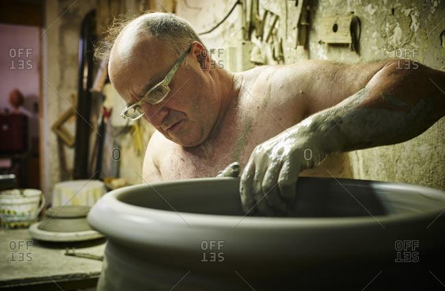 Potter in workshop working on large terracotta vase