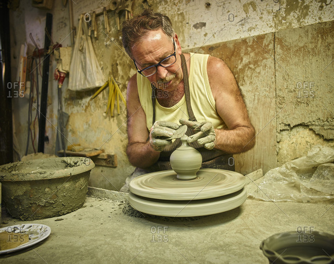 Potter in workshop working on earthenware vessel
