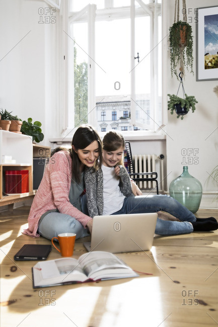 Mother and daughter at home sitting on floor using laptop
