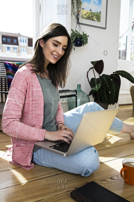 Woman at home sitting on floor using laptop