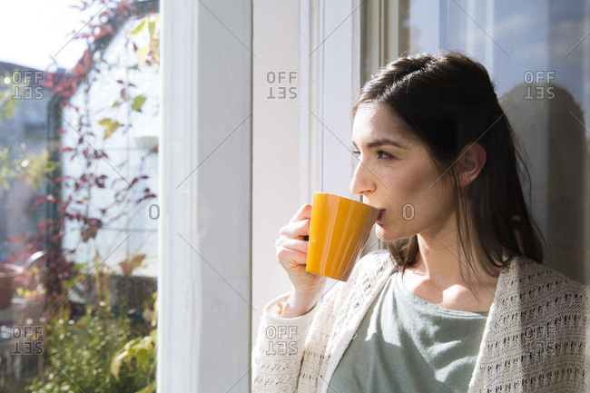 Woman drinking coffee at the window