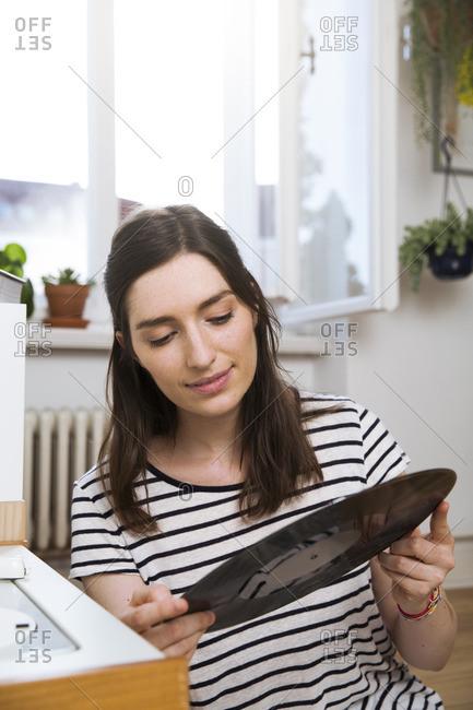 Woman at home looking at record