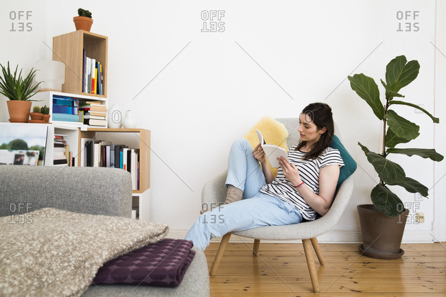 Woman at home sitting on chair reading book