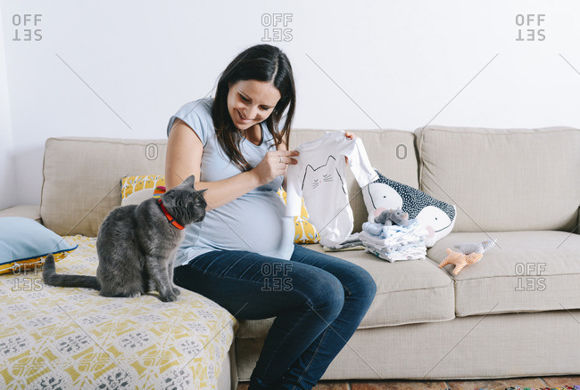 Pregnant woman with cat sitting on couch- looking at baby sleepers