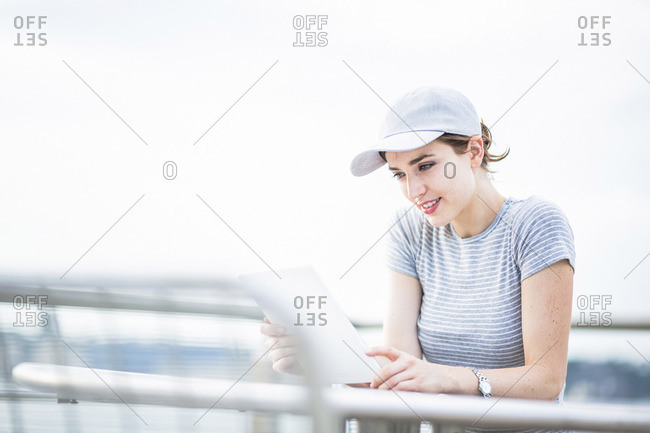 Woman with basecap looking at tablet