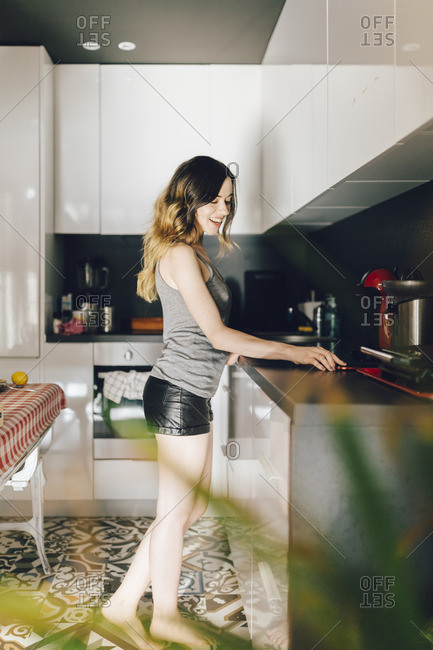 Smiling young woman in kitchen