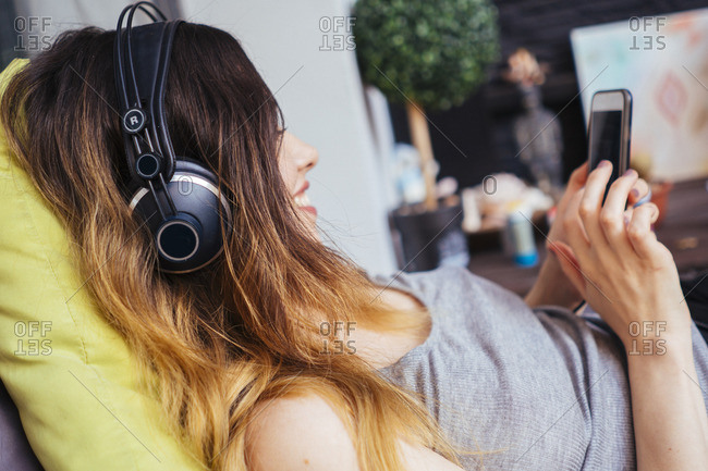 Young woman wearing headphones using cell phone