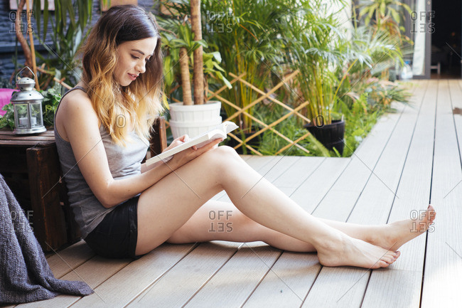 Relaxed Young Woman Reading Book On Terrace Stock Photo - Offset-3270