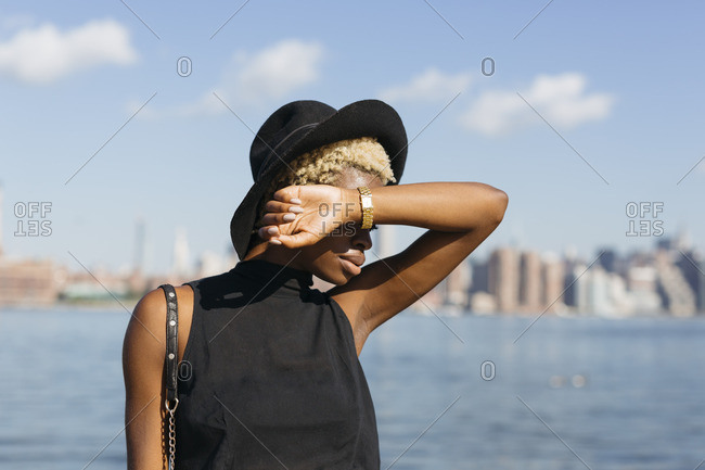 USA- New York City- Brooklyn- young woman at East River wearing a hat