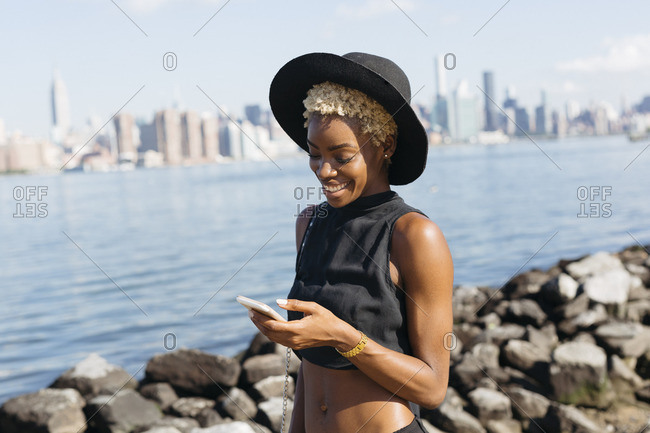 USA- New York City- Brooklyn- smiling young woman at East River looking on cell phone