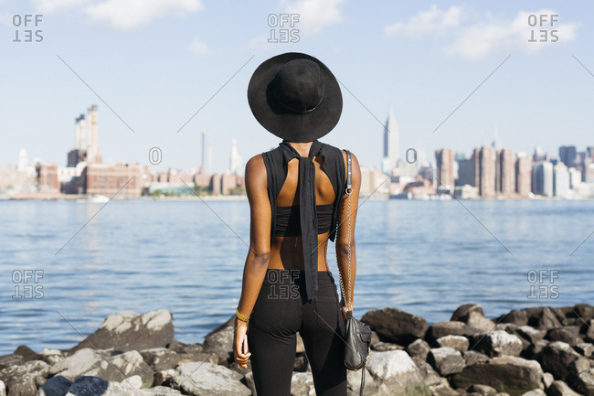 USA- New York City- Brooklyn- young woman standing at East River