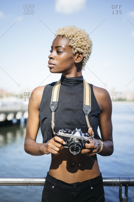Young woman with camera at the waterfront looking around